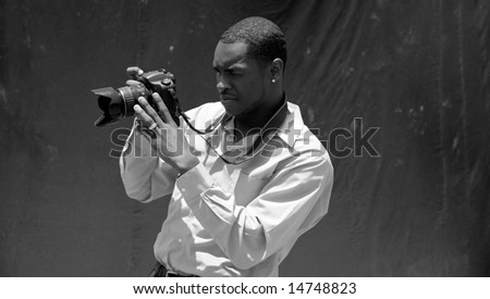 a photographer reviews what he just captured on his Digital Camera Review Screen in black and white