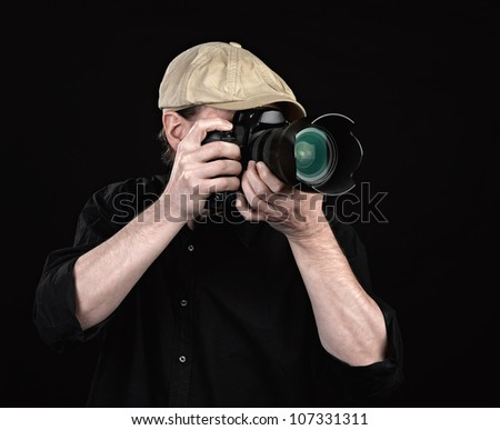 A photographer with a nice camera on black background - stock photo