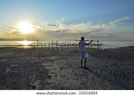 A photographer with his tripod near a lake at sunset. - stock photo