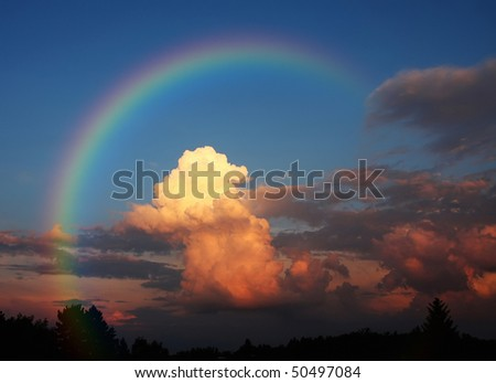 A photography of a white cloud in the evening sun under a rainbow - stock photo