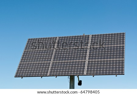A photovoltaic solar panel array in a park with a deep blue sky in the background. Clean, renewable energy. - stock photo