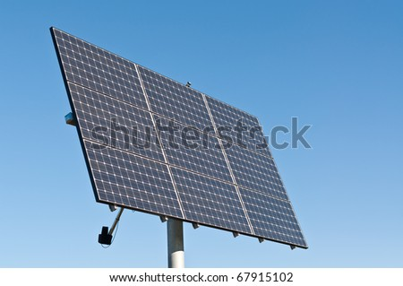 A photovoltaic solar panel array in a park with a deep blue sky in the background. Clean, renewable energy.