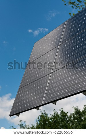 A photovoltaic solar panel array  with a blue sky and green leaves in the background. - stock photo