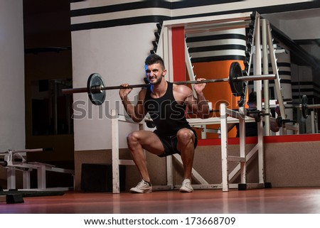 A Physically Fit Men Exercising By Doing Squats - stock photo