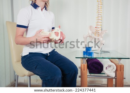 A physiotherapist is sitting in her office and is holding a model of the human pelvis - stock photo