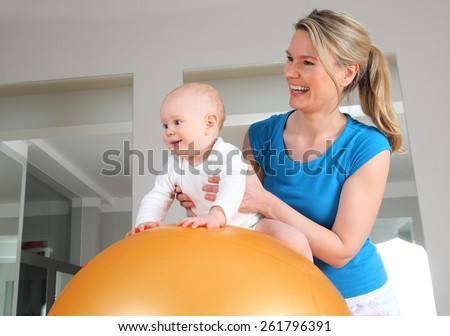 A Physiotherapy with Baby on a Fitness Ball - stock photo