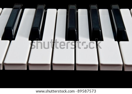 a piano keyboard isolated on a black background - stock photo