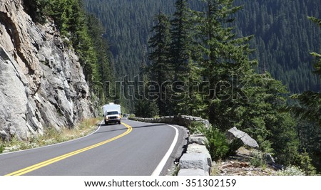 A pickup pulling an RV on a paved road at high elevations in Rainier National Park. - stock photo