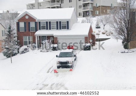 A pickup truck equipped with a plow and a salt thrower is removing snow from a sloped driveway in winter. - stock photo