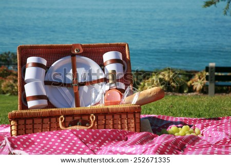 A Picnic at the beach with Wine, French Bread, Green Grapes, Mozzarella Cheese, Wine Glasses, Wicker Picnic Basket, Pink Pokka dot Cloth, Plates, Cups, Green Grass and the Blue Ocean.    - stock photo
