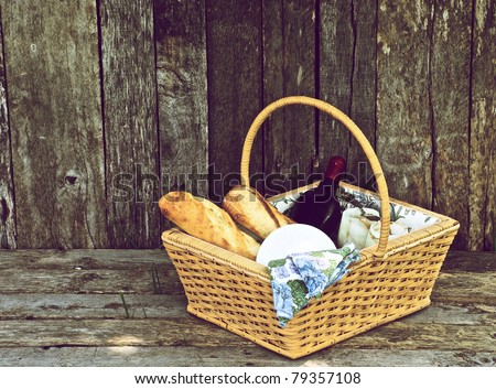 A picnic  for two with wine, bread and cheese in a ceramic holder on a wooden background. - stock photo
