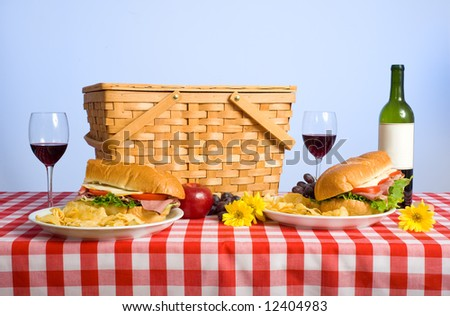 A picnic lunch on a red and white gingham tablecloth including a sandwich, chip, grapes wine and a picnic basket in front of a blue sky background - stock photo