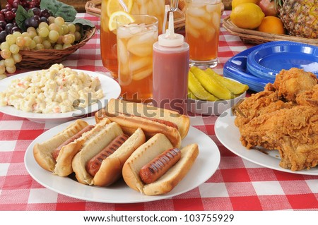 A picnic table loaded with summer foods - stock photo