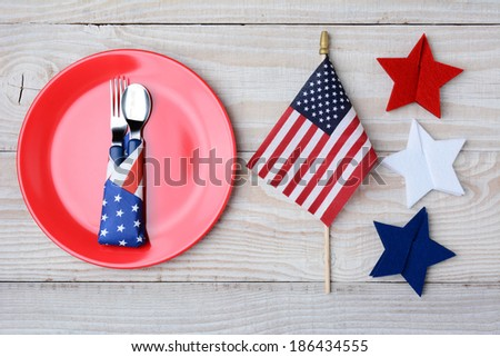 A picnic table ready for a 4th of July picnic. A red plate with fork and spoon, American Flag and felt stars decorate the table. - stock photo