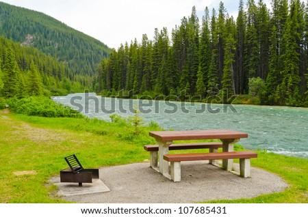 A picnic table with gorgeous view at mountain river, British Columbia, Canada. - stock photo