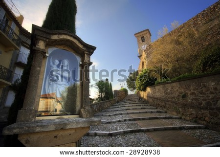 A pictoresque street of the Old Cannes with tthe ancient belltower and clock and a close view of an old statue of Mary - stock photo