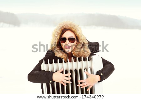 A picture of a beautiful woman hugging a radiator in winter - stock photo