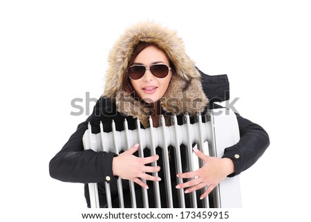 A picture of a beautiful woman hugging a radiator over white background - stock photo