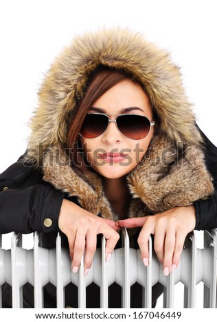 A picture of a beautiful woman sitting close to a radiator over white background - stock photo