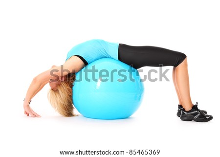 A picture of a beautiful young woman making a bridge on a ball over white background
