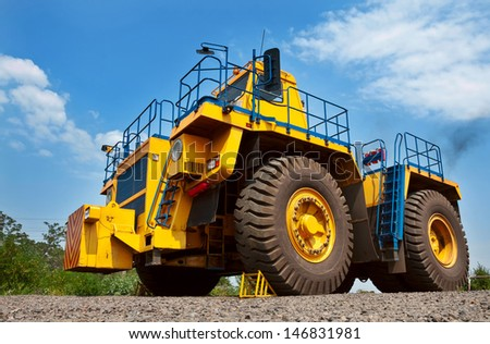 A picture of a big yellow mining truck at work site on blue sky with white clouds background - stock photo
