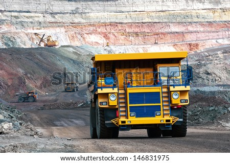 A picture of a big yellow mining trucks at work site - stock photo