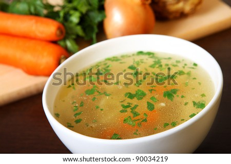 A picture of a bowl of traditional chicken soup served in a bowl over vegetable background