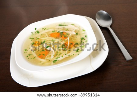 A picture of a bowl of traditional Polish chicken soup served in a bowl over wooden background - stock photo