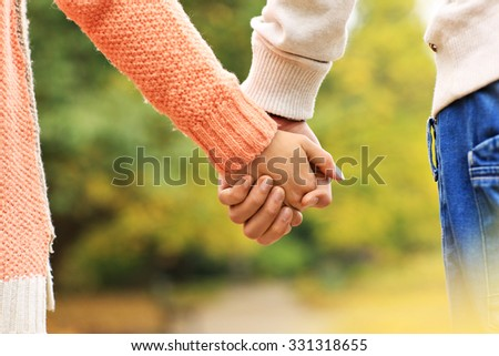 A picture of a couple holding hands in the park - stock photo