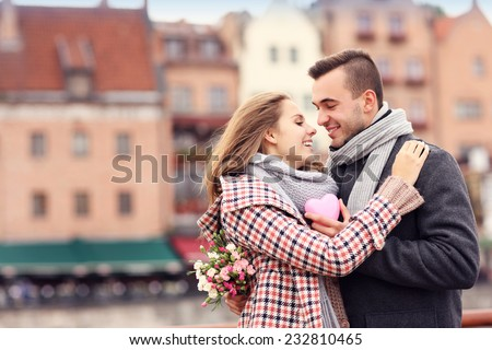 A picture of a couple on Valentine's Day in the city with flowers and heart - stock photo