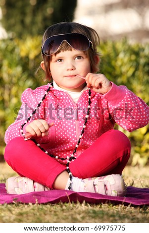 A picture of a cute baby girl putting on a lip gloss and playing with mum's necklace in the park - stock photo