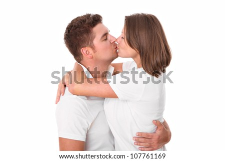 A picture of a cute young couple kissing over white background - stock photo