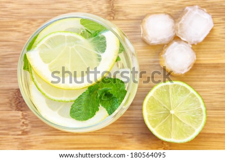 A picture of a glass of water with lemon lime and mint served with ice cubes on a wooden board - stock photo