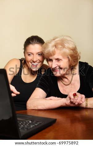 A picture of a granddaughter showing something on the laptop to her grandma - stock photo