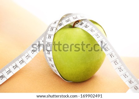 A picture of a green apple with tape measure on a female back - stock photo