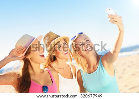 A picture of a group of friends drinking beer and taking selfie on the beach - stock photo