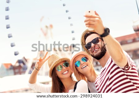 A picture of a group of friends hanging out in the city and taking selfie - stock photo