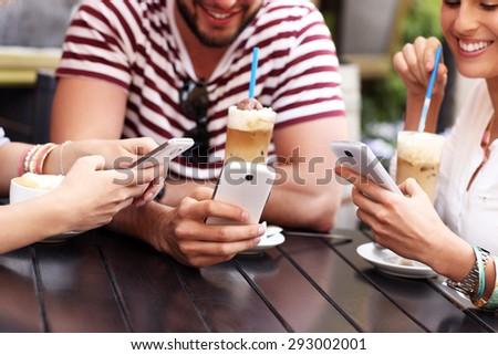 A picture of a group of friends resting in an outdoor cafe and using smartphones - stock photo