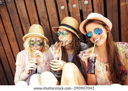 A picture of a group of girl friends drinking soda on the pier - stock photo