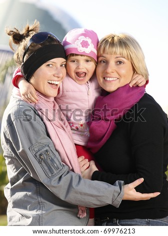 A picture of a happy baby girl spending time in the park with her mum and aunt - stock photo