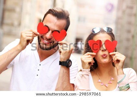 A picture of a happy couple covering eyes with hearts - stock photo
