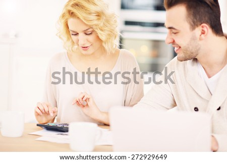 A picture of a happy couple planning home budget in the kitchen - stock photo