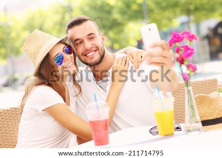 A picture of a happy couple taking selfie in a cafe - stock photo