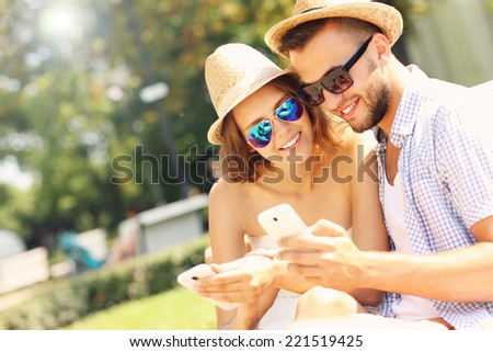 A picture of a happy couple with smartphones in the park - stock photo