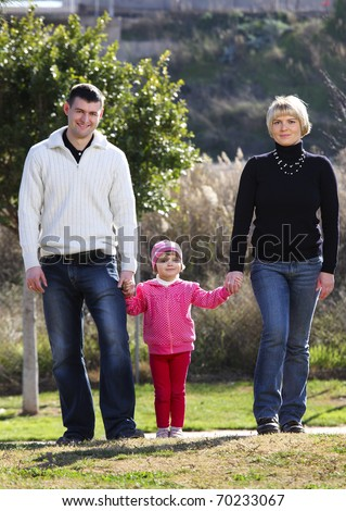 A picture of a happy family walking together in the park - stock photo