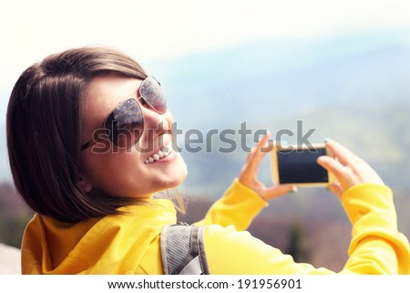 A picture of a happy tourist taking pictures in the mountains - stock photo