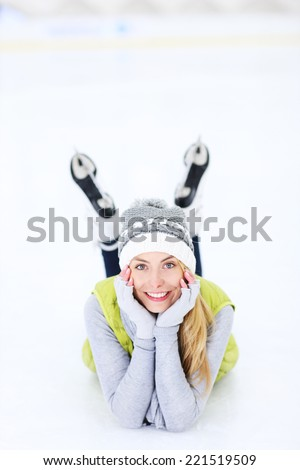 A picture of a happy woman lying on the ice rink - stock photo