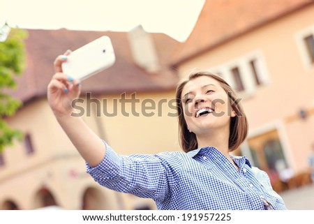 A picture of a happy woman taking selfie in Bardejov town in Slovakia - stock photo