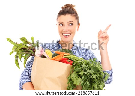 A picture of a happy woman with vegetables pointing at something over white background