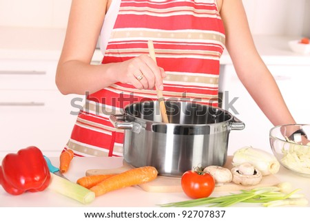 A picture of a housewife preparing soup in a pot in the kitchen
